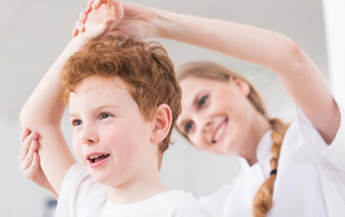 A young child with curly red hair has their arm stretched carefully by a smiling female practitioner as part of movement therapy.