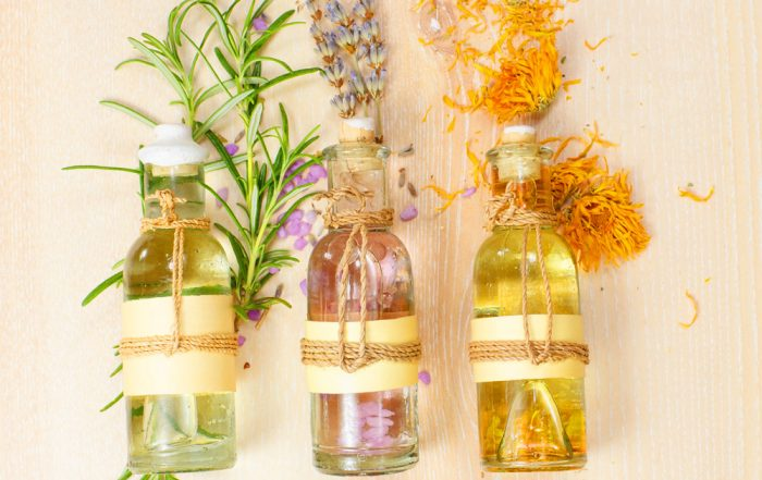 Three corked bottles with small ropes tied around, filled with essential oils with various aromatic plants behind the bottles