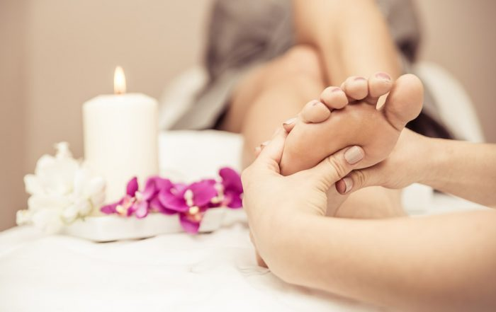 A woman sitting back has her foot massaged. To the left are white candles and white and pink flowers.