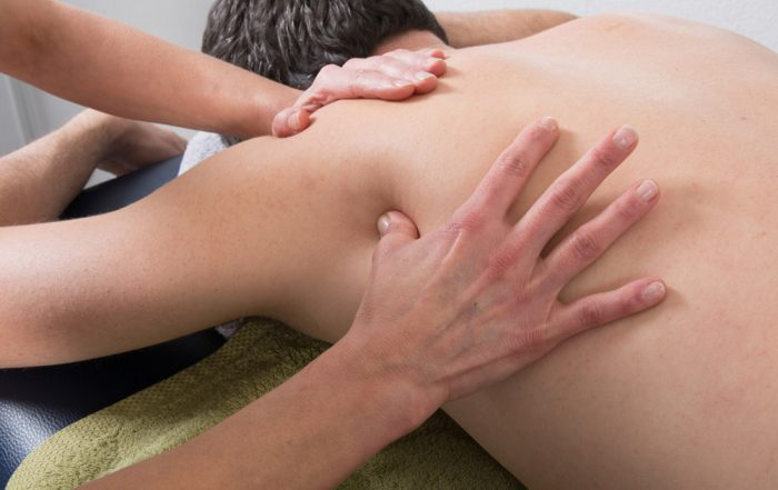Person laying on their front receives a Shiatsu massage from a therapist.