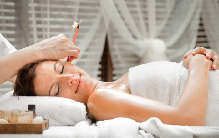 Woman laying on her back with a towel on her body and her head titled to the side while an Ear Candling practitioner holds an ear candle in her ear.