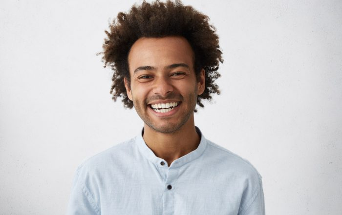 A man of African descent smiling brightly at the camera on a soft gray background