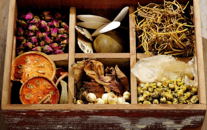 Wooden box with six evenly sized compartments filled with an assortment of Asian dried herbs, mushrooms and flowers