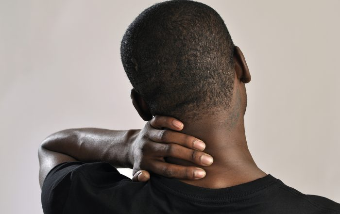 Closeup of man rubbing his neck with hand as he aches with pain in the neck on grey background