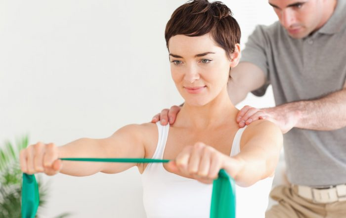 A white woman has both arms stretched outward while she grips a green or turquoise piece of fabric and stretches it taught. A man stands behind her with his hands on her shoulders and looking at her back.