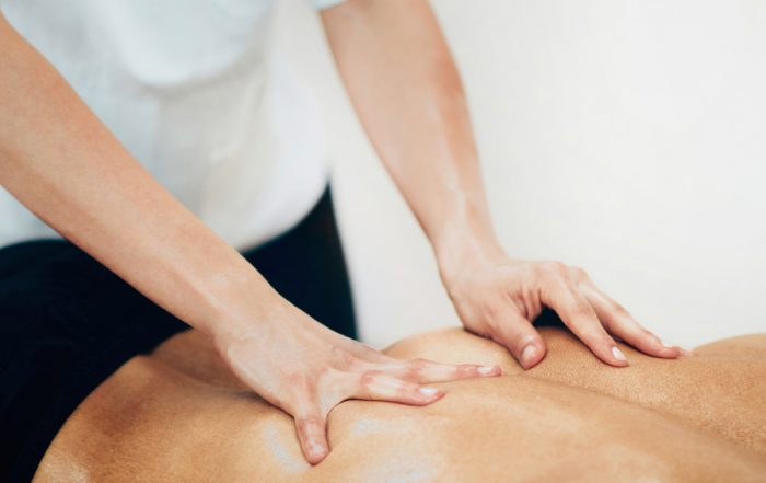 Caucasian practitioner giving a back massage to a caucasian male.
