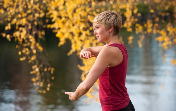 A woman in a red top and black leggings is practicing Tai Chi in front of a lake. Yellow gold leaves hanging from a tree are blurred in the background behind the woman.