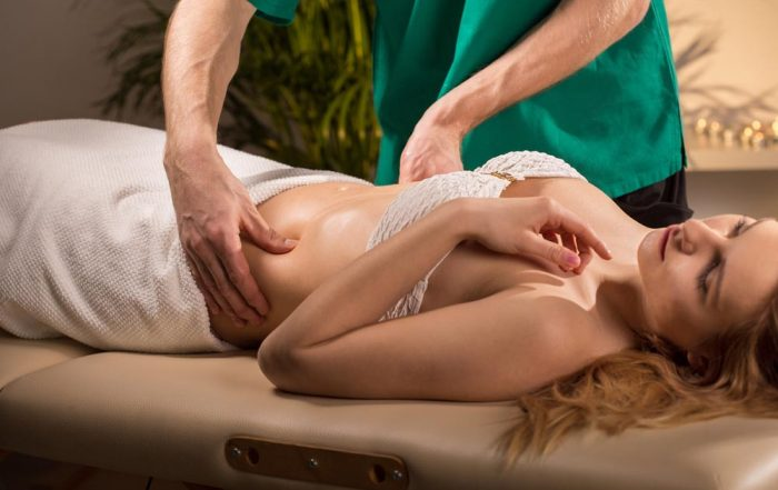 A woman laying on her back on a massage table. She's wearing a bra and has a towel covering her from the hips down. A practitioner in green scrubs is massaging her abdominal area.