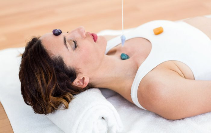 Caucasian woman laying on her back wearing a white top with various crystals on her forehead, throat and chest, with a crystal hanging from a thread above her throat