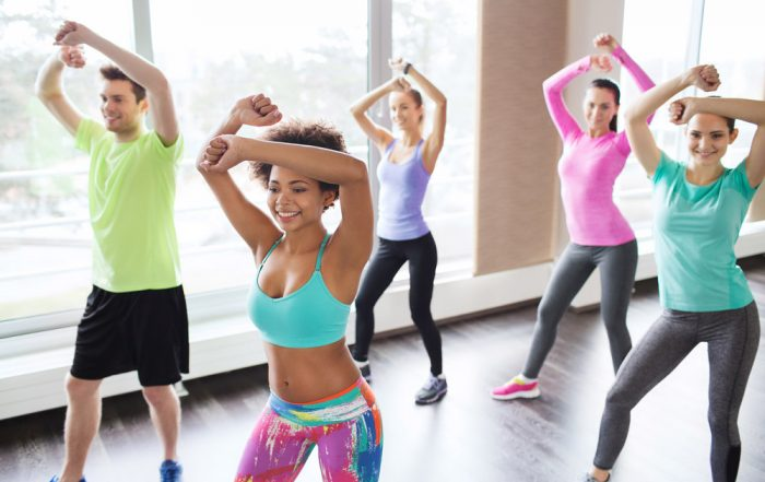 Four women and one man all have their arms raised over their heads in the middle of movement. They are wearing colorful workout clothing and shoes.