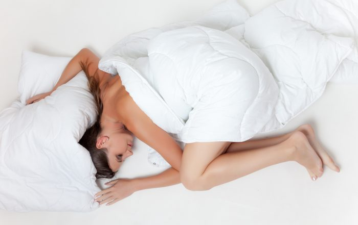 A woman is laying on a bed covered by a white duvet. She's curled up in a fetal position with her arms on either side of her body. Her head is laying below the pillow.