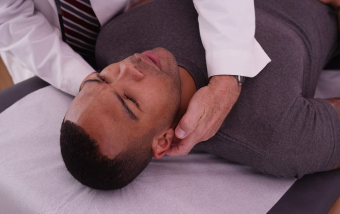 Man of African descent is laying on his back on a massage table. A practitioner is touching his neck.