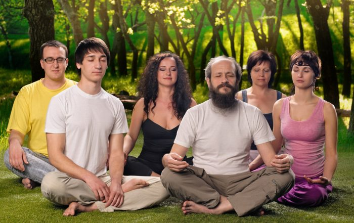 A group of Caucasian people sitting cross legged on a grassy floor in front of a background of trees with sunshine. They have their eyes closed and are meditating.
