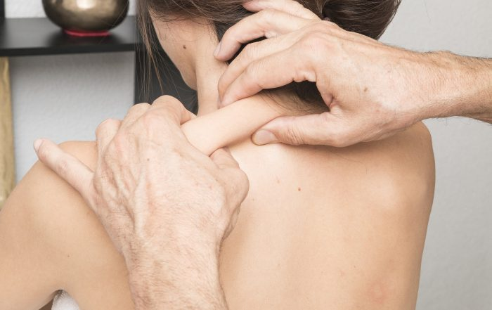 A Caucasian woman's bare back is facing the camera while a practitioner is pinching the tissue between her neck and shoulder.