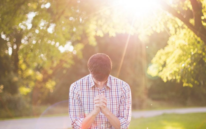 Man bowing head with hands folded in front of the sun shining into camera