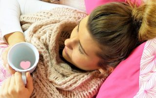Woman bundled up with scarf holding a cup of water with a pink heart in water