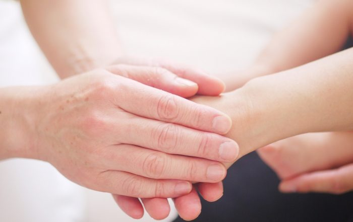 Caucasian person's hands holding another caucasian person's hand