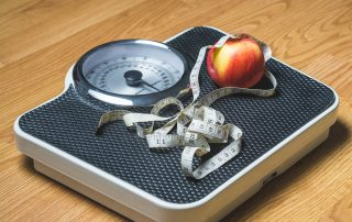 Human scale with an apple and measuring tape resting on top