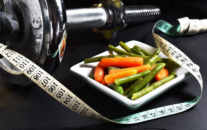 A lifting weight is laying next to a bowl of steamed green beans and carrots. In front of both is a measuring tape showing centimeters.