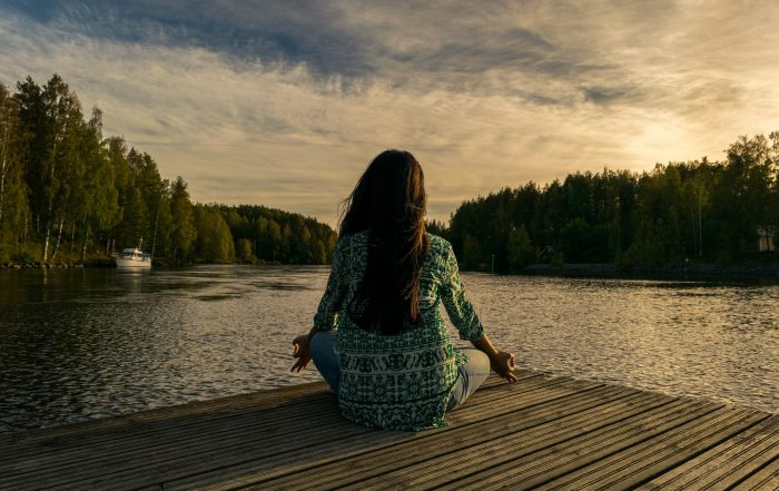 A woman sits with her back to the camera, cross legged in front of a lake on a wooden deck. The sun is setting behind trees in the background.