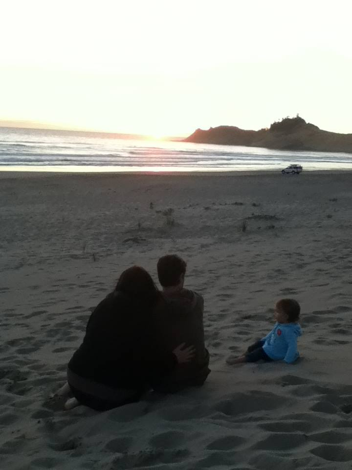 Two adults and a toddler on a beach