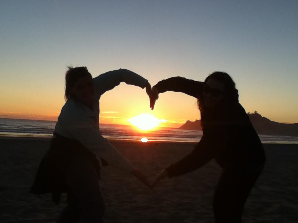 Two people in front of a sunset creating a heart shape with their arms