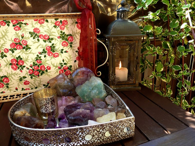 Heart shaped tray with various crystals and a candle on a wooden table with a second candle in a lantern beside the tray